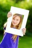 Χαριτωμένο εύθυμο μικρό κορίτσι που κρατά το άσπρο πλαίσιο εικόνων μπροστά από το πρόσωπό της Στοκ φωτογραφία με δικαίωμα ελεύθερης χρήσης