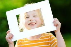 Χαριτωμένο εύθυμο μικρό κορίτσι που κρατά το άσπρο πλαίσιο εικόνων μπροστά από το πρόσωπό της Στοκ Εικόνες