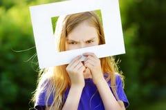 Χαριτωμένο εύθυμο μικρό κορίτσι που κρατά το άσπρο πλαίσιο εικόνων μπροστά από το πρόσωπό της Στοκ εικόνα με δικαίωμα ελεύθερης χρήσης