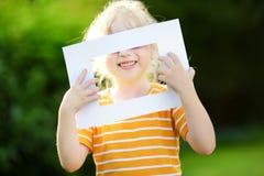 Χαριτωμένο εύθυμο μικρό κορίτσι που κρατά το άσπρο πλαίσιο εικόνων μπροστά από το πρόσωπό της Στοκ Φωτογραφία