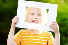 Χαριτωμένο εύθυμο μικρό κορίτσι που κρατά το άσπρο πλαίσιο εικόνων μπροστά από το πρόσωπό της Στοκ Φωτογραφίες