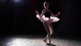 Χαριτωμένο εύκαμπτο ballerina που χορεύει στα παπούτσια μπαλέτου pointe της στο επίκεντρο στο μαύρο υπόβαθρο στο στούντιο Το κορί φιλμ μικρού μήκους