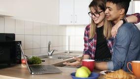 Χαριτωμένο ζεύγος δύο νέων που αγκαλιάζουν και που χρησιμοποιούν το lap-top, που κάνει σερφ τον Ιστό στην κουζίνα Νεολαία, σχέση, φιλμ μικρού μήκους