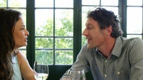 Χαριτωμένο ζεύγος που έχει το μεσημεριανό γεύμα και που ψήνει με το κρασί απόθεμα βίντεο