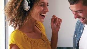 Χαριτωμένο ζεύγος που ακούει τη μουσική με τα ακουστικά και το χορό απόθεμα βίντεο