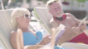 Χαριτωμένο ζεύγος που βρίσκεται στα sunbeds κοντά στη λίμνη Ωριμάστε τη γυναίκα που διαβάζει ένα βιβλίο ενώ ηληκιωμένος που εξετά φιλμ μικρού μήκους
