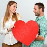 Χαριτωμένο ζεύγος που κρατά το μεγάλο κόκκινο σημάδι καρδιών. Στοκ Εικόνες