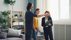 Χαριτωμένο ζεύγος που συζητά τη σύμβαση υποθηκών με το realtor που μιλά στο εσωτερικό στο σπίτι απόθεμα βίντεο