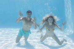 Χαριτωμένο ζεύγος που χαμογελά στη κάμερα υποβρύχια στην πισίνα στοκ φωτογραφίες με δικαίωμα ελεύθερης χρήσης