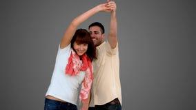 Χαριτωμένο ζεύγος που χορεύει στο γκρίζο υπόβαθρο απόθεμα βίντεο