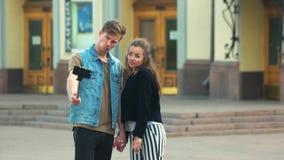 Χαριτωμένο ζεύγος τουριστών που παίρνει την εικόνα μαζί στην πόλη απόθεμα βίντεο