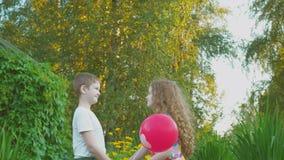 Χαριτωμένο ζεύγος φίλων με το μπαλόνι καρδιών στο θερινό πάρκο απόθεμα βίντεο