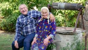 Χαριτωμένο ηλικιωμένο ζεύγος που αγκαλιάζει και που χαμογελά υπαίθρια απόθεμα βίντεο