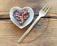 Χαριτωμένο διαμορφωμένο καρδιά κομμάτι του κέικ σοκολάτας που ψεκάζεται με τα λουλούδια Στοκ Φωτογραφία