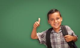 Χαριτωμένο ισπανικό αγόρι μπροστά από τον κενό πίνακα κιμωλίας Στοκ Φωτογραφία