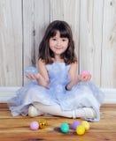 χαριτωμένο κάθισμα χεριών κοριτσιών αυγών Πάσχας Στοκ Φωτογραφίες