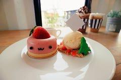 Χαριτωμένο κέικ, cheesecake φραουλών που διακοσμείται με το πρόσωπο smiley που εξυπηρετείται με το παγωτό βανίλιας στοκ φωτογραφίες