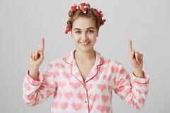 Χαριτωμένο και θηλυκό ευρωπαϊκό κορίτσι στα τρίχα-ρόλερ και nightwear, δείχνοντας επάνω με τους αντίχειρες, χαμογελώντας και κοιτ στοκ εικόνες με δικαίωμα ελεύθερης χρήσης