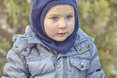 Χαριτωμένο καυκάσιο αγόρι liittle με τα μεγάλα φωτεινά μπλε μάτια στα χειμερινά ενδύματα και κουκούλα καπέλων στο πράσινο υπόβαθρ στοκ εικόνες