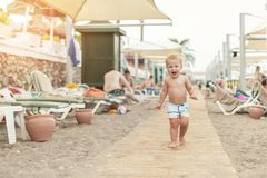Χαριτωμένο καυκάσιο αγόρι toodler που περπατά μόνο στην αμμώδη παραλία μεταξύ του μόνιππο-σαλονιού Λατρευτό ευτυχές παιδί που έχε στοκ εικόνα
