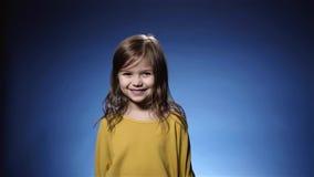Χαριτωμένο κομφετί γέλιου μικρών κοριτσιών που πέφτει, κροτίδα, μπλε υπόβαθρο σε αργή κίνηση απόθεμα βίντεο