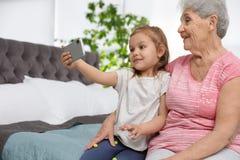 Χαριτωμένο κορίτσι και η γιαγιά της που παίρνουν selfie στοκ φωτογραφίες με δικαίωμα ελεύθερης χρήσης
