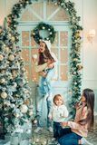 Χαριτωμένο κορίτσι και η μητέρα της που διακοσμούν firtree στη Παραμονή Χριστουγέννων στοκ εικόνες
