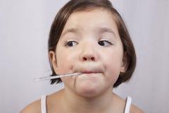 Χαριτωμένο κορίτσι με ένα κλινικό θερμόμετρο υδράργυρος--γυαλιού στοκ εικόνα με δικαίωμα ελεύθερης χρήσης