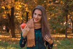 Χαριτωμένο κορίτσι με ένα μαντίλι στους ώμους του χαμόγελου και του κρατήματος της Apple Στοκ εικόνα με δικαίωμα ελεύθερης χρήσης