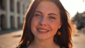 Χαριτωμένο κορίτσι με την κόκκινη τρίχα και φακίδες στην οδό Μεγάλη κεντρική οδός πόλεων Φωτισμός ανατολής απόθεμα βίντεο