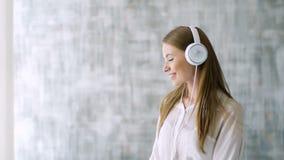 Χαριτωμένο κορίτσι με τους άσπρους χορούς ακουστικών στο δωμάτιο απόθεμα βίντεο