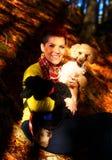 Χαριτωμένο κορίτσι με το γραπτό σκυλί που χαμογελά και που αγκαλιάζει στο δάσος φθινοπώρου υπαίθρια Οπτική επαφή Στοκ Εικόνα