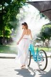 Χαριτωμένο κορίτσι με το ποδήλατο στο πλαίσιο του misty συστήματος του θερινού καφέ Στοκ Φωτογραφία