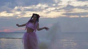 Χαριτωμένο κορίτσι με το φωτεινό makeup στο ρόδινο φόρεμα που χορεύει στην ιξώδη υδρονέφωση από τις βόμβες καπνού υπαίθρια Ο χορό απόθεμα βίντεο