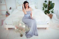 Χαριτωμένο κορίτσι με το makeup σε μια μπλε συνεδρίαση φορεμάτων βραδιού στο κρεβάτι Στα χέρια που κρατούν ένα κερί Στοκ Φωτογραφίες