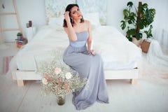 Χαριτωμένο κορίτσι με το makeup σε μια μπλε συνεδρίαση φορεμάτων βραδιού στο κρεβάτι Στα χέρια που κρατούν ένα κερί Στοκ Φωτογραφία
