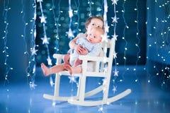 Χαριτωμένο κορίτσι μικρών παιδιών και το νεογέννητο brotherin μωρών της ένα σκοτεινό δωμάτιο με τα φω'τα Χριστουγέννων Στοκ Εικόνα