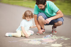Χαριτωμένο κορίτσι μικρών παιδιών και το σχέδιο πατέρων της με την κιμωλία χρώματος Στοκ Εικόνες