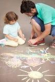 Χαριτωμένο κορίτσι μικρών παιδιών και το σχέδιο πατέρων της με την κιμωλία χρώματος Στοκ φωτογραφία με δικαίωμα ελεύθερης χρήσης