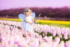 Χαριτωμένο κορίτσι μικρών παιδιών στο κοστούμι νεράιδων σε έναν τομέα λουλουδιών Στοκ φωτογραφία με δικαίωμα ελεύθερης χρήσης