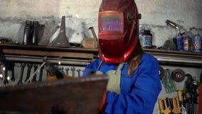 Χαριτωμένο κορίτσι οξυγονοκολλητών σε ομοιόμορφο στο γκαράζ που λειτουργεί με τον εξοπλισμό συγκόλλησης Εργασία γυναικών ` s στην φιλμ μικρού μήκους