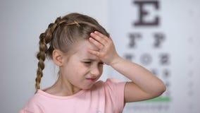Χαριτωμένο κορίτσι παιδιών που υφίσταται τον πονοκέφαλο, πρώτο σύμπτωμα μυωπίας, απώλεια όρασης απόθεμα βίντεο