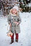 Χαριτωμένο κορίτσι παιδιών με τον τροφοδότη πουλιών και σπόροι στο χειμερινό χιονώδη κήπο Στοκ Εικόνες