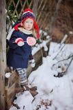 Χαριτωμένο κορίτσι παιδιών στο καπέλο Χριστουγέννων με την καραμέλα στο χειμερινό χιονώδη κήπο Στοκ φωτογραφία με δικαίωμα ελεύθερης χρήσης