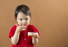 Χαριτωμένο κορίτσι παιδιών τα γλυκά donuts που απομονώνονται που τρώει στοκ εικόνες