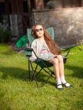 Χαριτωμένο κορίτσι που έχει sunbath στην καρέκλα στη χλόη Στοκ Εικόνες