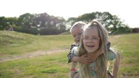 Χαριτωμένο κορίτσι που δίνει το γύρο σηκώνω στην πλάτη αγοριών μικρών παιδιών στο πάρκο απόθεμα βίντεο
