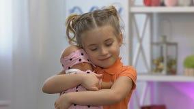 Χαριτωμένο κορίτσι που αγκαλιάζει tenderly το αγαπημένο παιχνίδι μωρών, που ονειρεύεται για λίγη αδελφή απόθεμα βίντεο