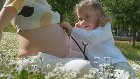 Χαριτωμένο κορίτσι που ακούει το έγκυο mom tummy φιλμ μικρού μήκους