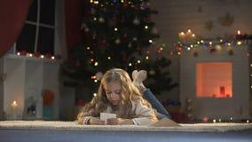 Χαριτωμένο κορίτσι που βάζει την επιστολή για Santa στο φάκελο, παιδαριώδης πεποίθηση στα Χριστούγεννα μαγικά φιλμ μικρού μήκους